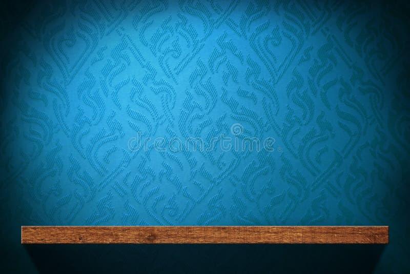 Prateleira de madeira vazia com o papel de parede retro azul imagens de stock royalty free