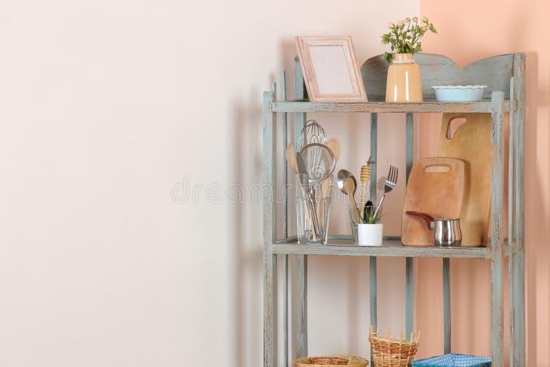 Prateleira do vintage com os pratos no canto da sala contra as paredes do branco e do pêssego prateleira antiga interior foto de stock royalty free