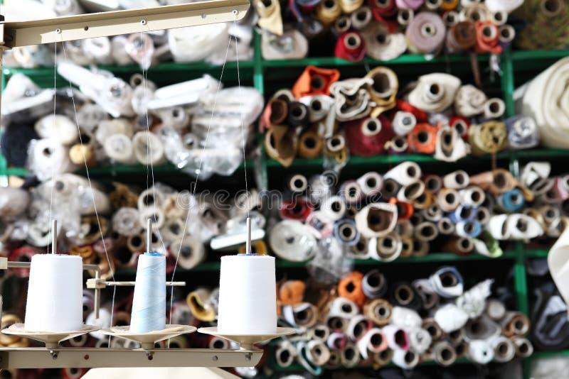 Prateleiras com rolos de telas coloridas e carretéis da linha de costura no primeiro plano foto de stock