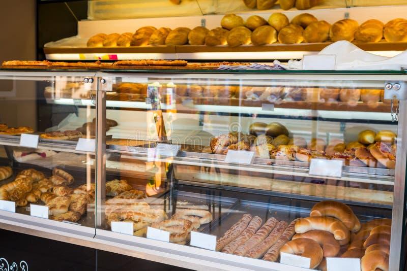 Prateleiras de vidro com pão fresco e bolos imagens de stock