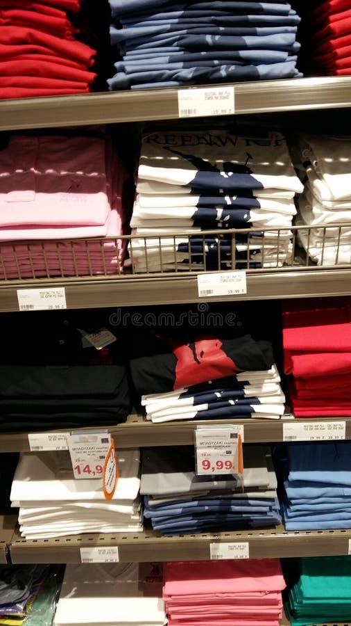 Prateleiras dos t-shirt no supermercado foto de stock