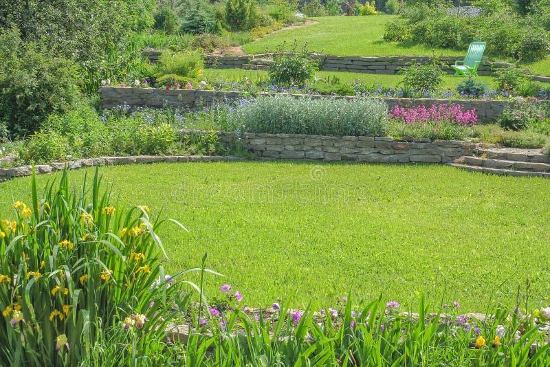 Prati inglesi e letti di fiore verdi nel giardino immagine stock