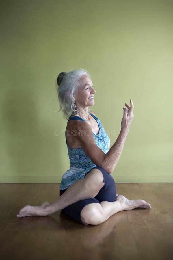 Pratica matura dello studio di yoga della donna immagine stock