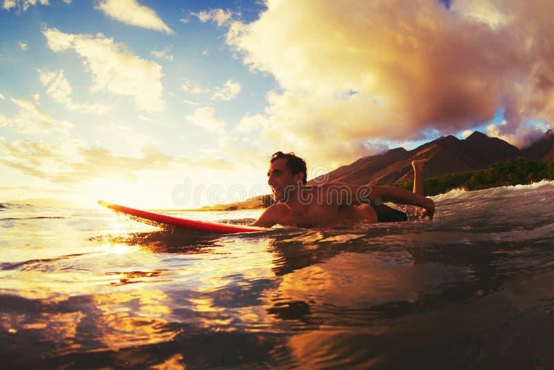 Praticando il surfing al tramonto fotografia stock libera da diritti