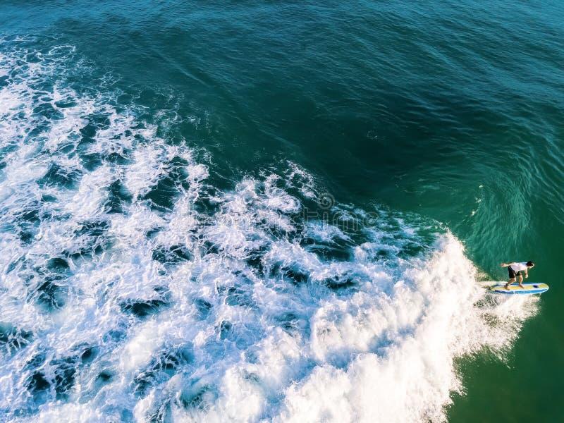 Praticando il surfing da solo nell'oceano immagini stock