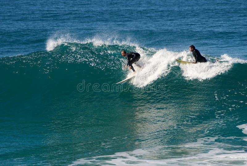 Praticando il surfing nei quarti vicini - viing per prendere un'onda fotografia stock