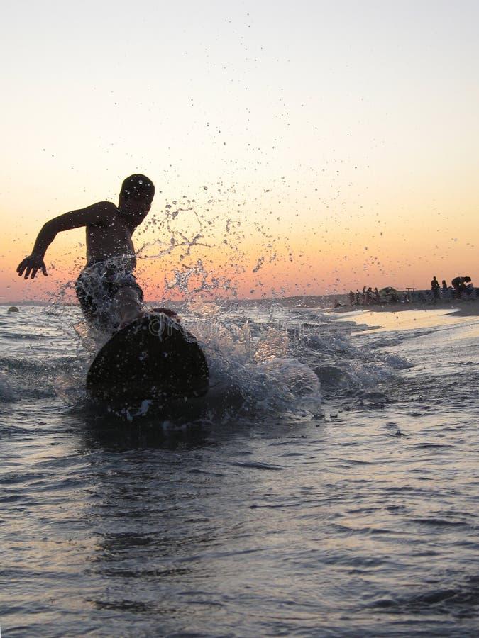 Praticando il surfing nella spiaggia immagine stock libera da diritti