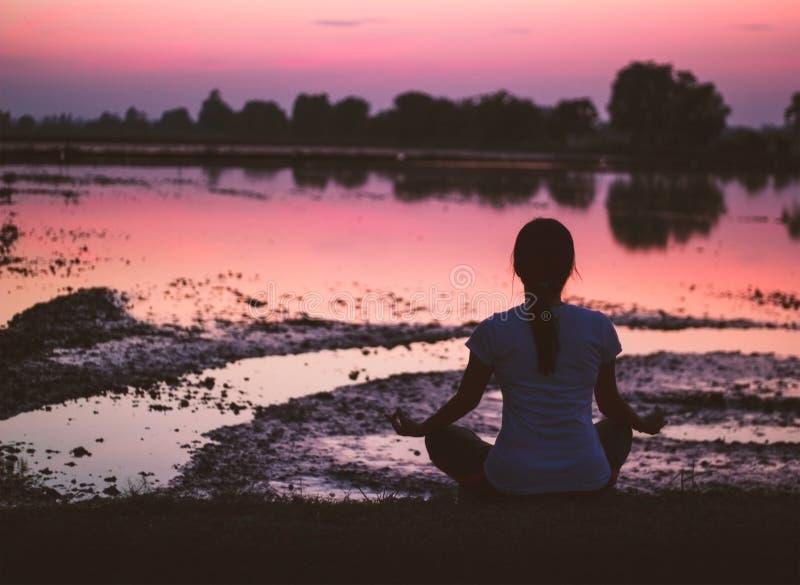 Praticar da serenidade e da ioga, meditando no fundo do por do sol imagem de stock