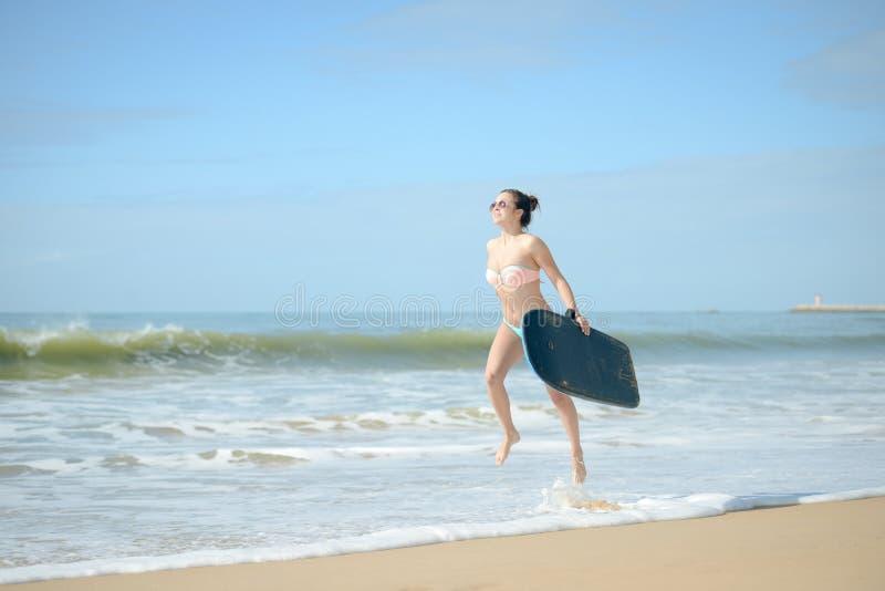 Praticare il surfing andante allegro felice della ragazza allegra del surfista alla spiaggia dell'oceano che si imbatte in acqua  immagini stock libere da diritti