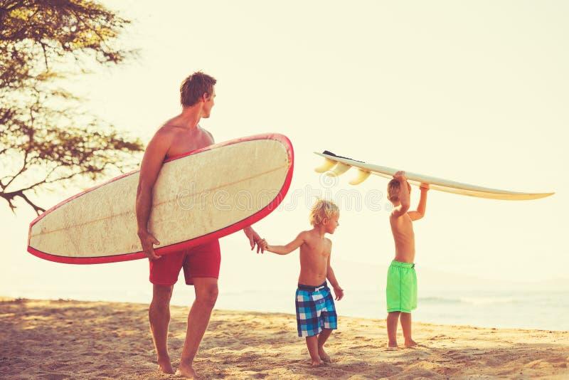 Praticare il surfing andante dei figli e del padre immagini stock libere da diritti