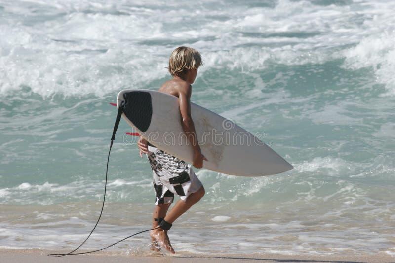 Praticare il surfing andante del giovane ragazzo immagini stock