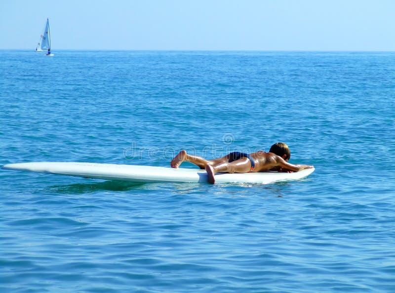 Praticare il surfing dentro si distende immagini stock