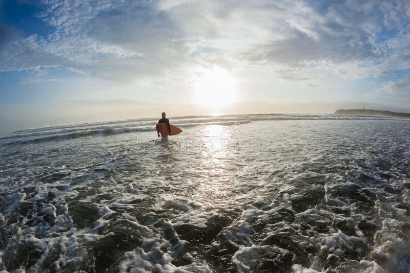 Praticare il surfing di mattina dell'oceano dell'entrata della spiaggia del surfista fotografie stock libere da diritti