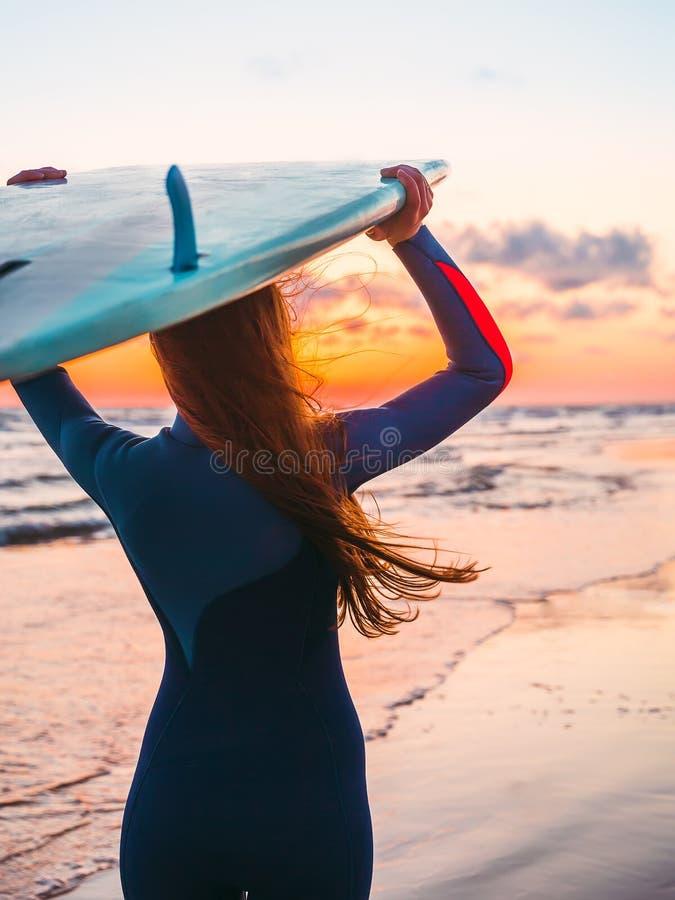 Pratichi il surfing la ragazza con capelli lunghi con il surf su una spiaggia al tramonto o l'alba ed oceano immagini stock libere da diritti