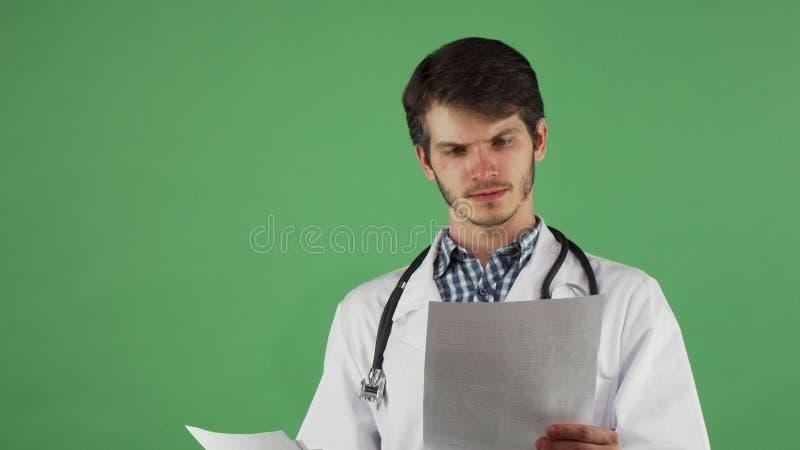 Praticien masculin attirant vérifiant les documents médicaux image stock