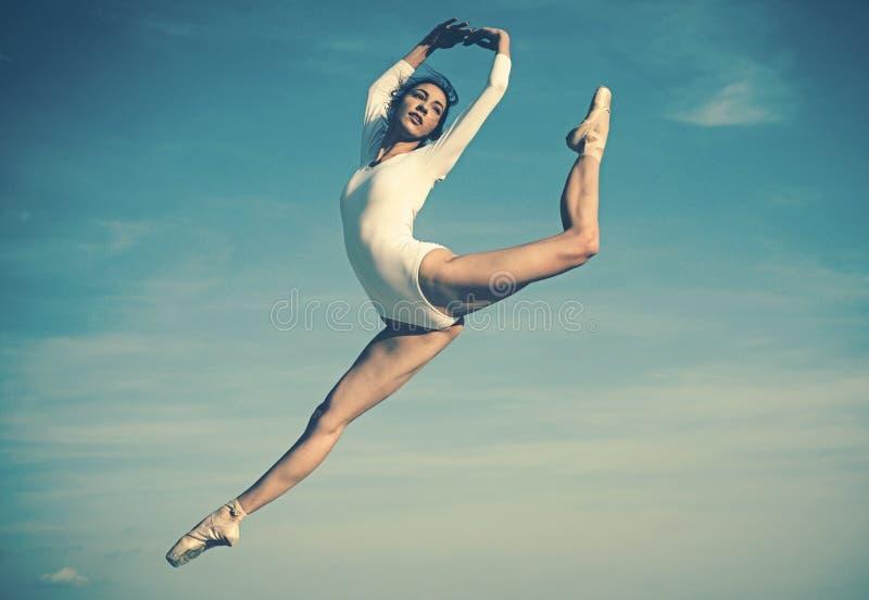 Pratique de l'art du ballet classique Jeune ballerine sautant sur le ciel bleu Jolie femme dans l'usage de danse Ballet mignon photographie stock libre de droits