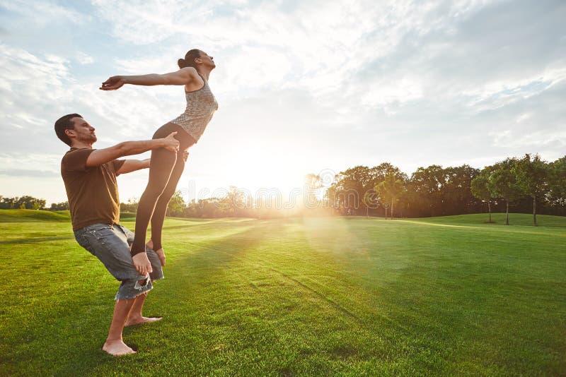 Pratique du vol Yoga de pratique d'acro de deux personnes en nature un matin ensoleillé Participation d'homme fort et femme de éq images libres de droits