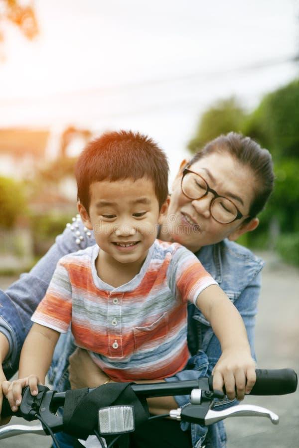 Pratique en matière asiatique de mère et de fils à la bicyclette de monte en parc public photos stock
