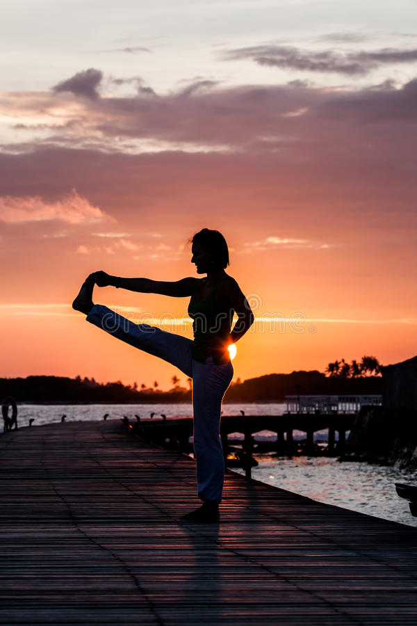 Pratique en matière de yoga pendant le coucher du soleil photos libres de droits