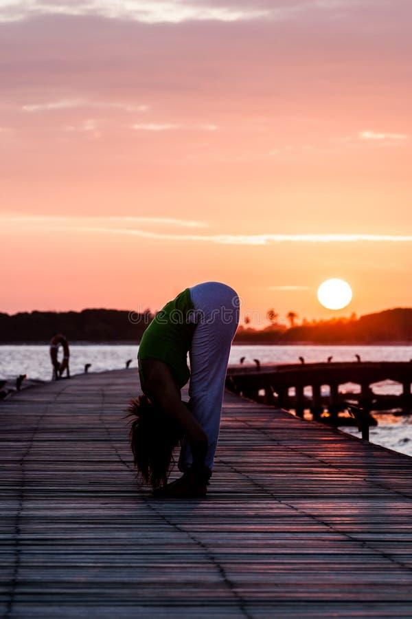 Pratique en matière de yoga pendant le coucher du soleil photos stock