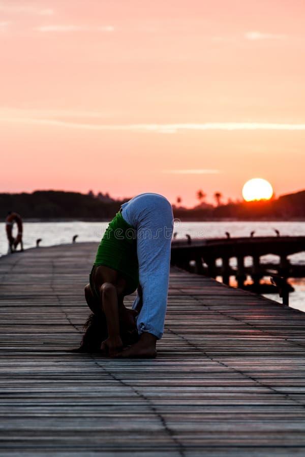 Pratique en matière de yoga pendant le coucher du soleil photographie stock