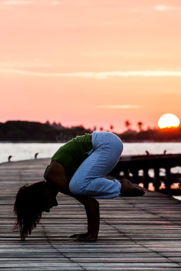 Pratique en matière de yoga pendant le coucher du soleil photo stock