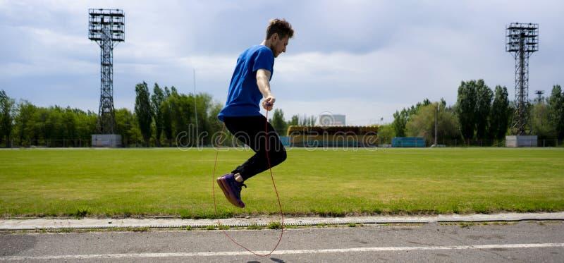 Pratique en matière masculine de sportif d'athlète avec la corde de saut aux stades extérieurs, vigueur d'augmentation photos stock