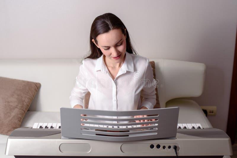 Pratique jogar o sintetizador, retrato frontal de uma mulher em um piano eletrônico imagem de stock royalty free