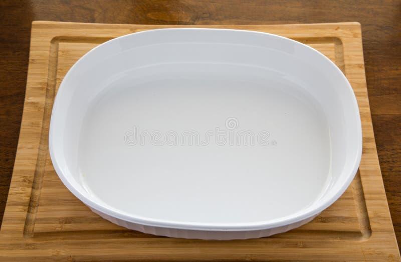 Prato branco vazio da caçarola na placa de corte de madeira fotografia de stock