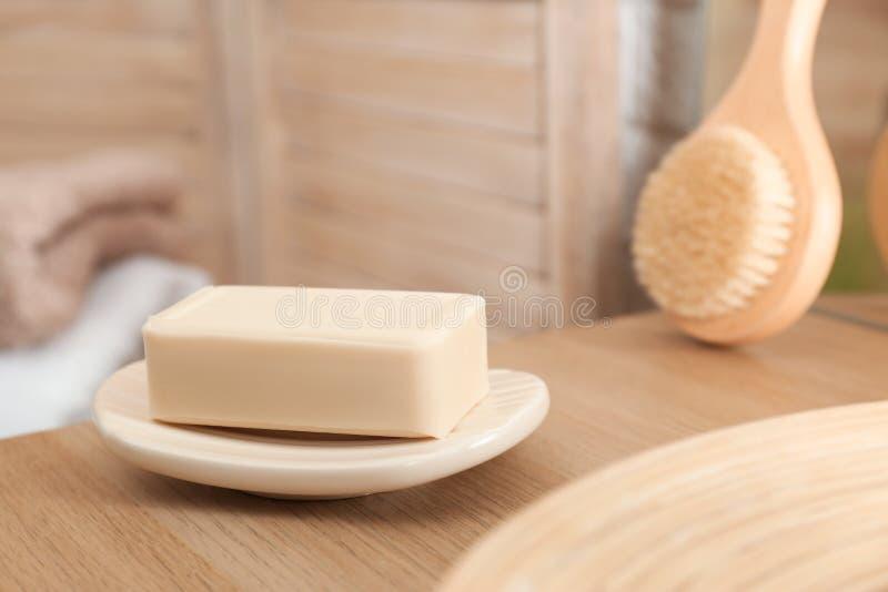 Prato com a barra do sabão na tabela de madeira imagem de stock royalty free
