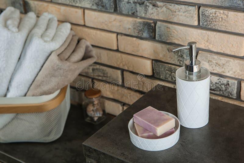 Prato com barras do sabão e garrafa do champô na tabela perto da parede de tijolo foto de stock royalty free