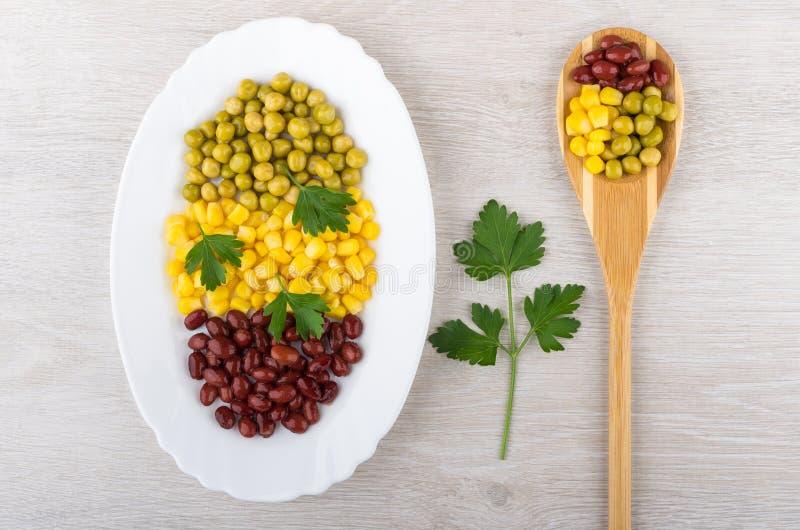Prato com ervilhas verdes, feijões, milho doce, salsa e colher fotos de stock