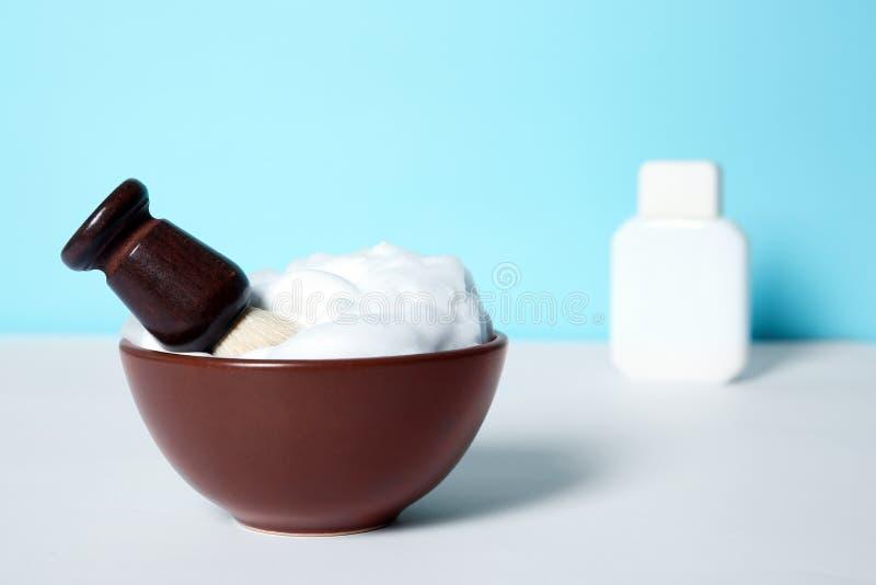 Prato com escova de rapagem e espuma na tabela branca fotografia de stock