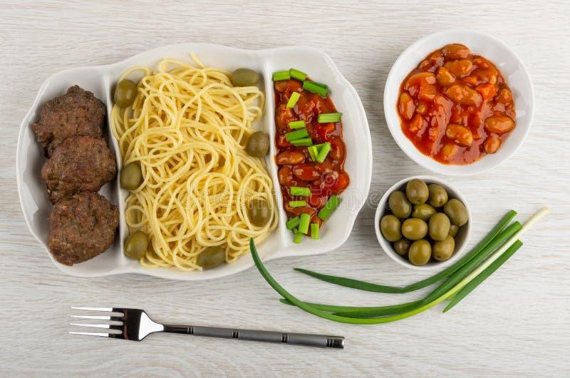 Prato com espaguetes, costoleta, feijões, cebola e azeitonas, bacias com feijões, azeitonas verdes, forquilha na tabela Vista sup foto de stock