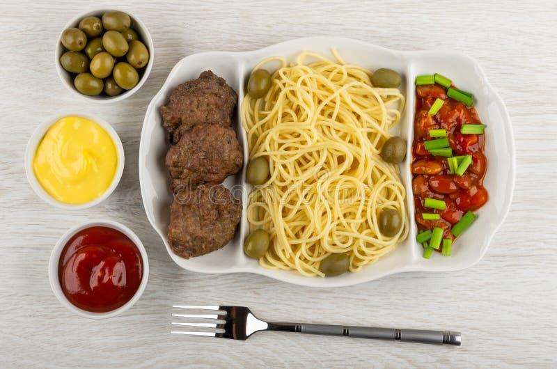 Prato com espaguetes, costoleta, feijões, a cebola verde e as azeitonas, ketchup, maionese, azeitonas verdes, forquilha na tabela fotos de stock