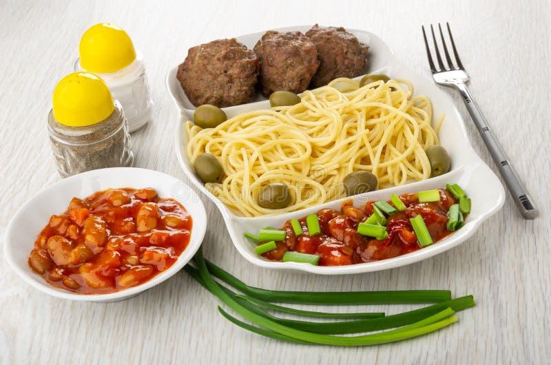 Prato com espaguetes, costoleta, feijões, a cebola verde e as azeitonas, pimenta, sal, bacia com feijões, forquilha na tabela imagens de stock