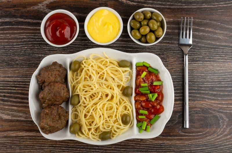 Prato com massa, costoleta, feijões, a cebola verde e as azeitonas, ketchup, maionese, azeitonas verdes, forquilha na tabela Vist imagem de stock royalty free