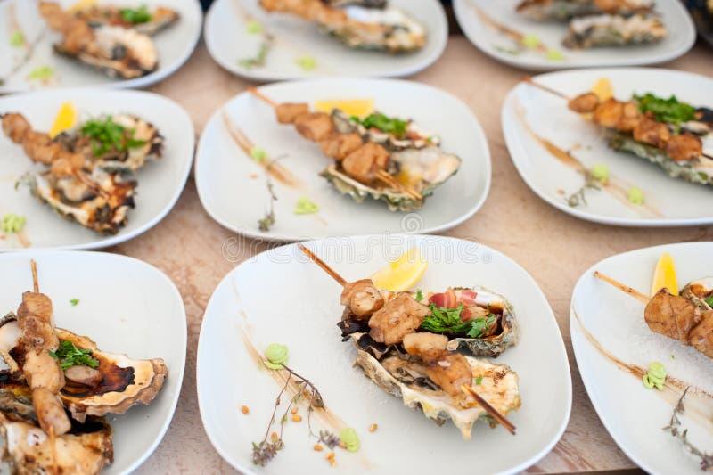 Prato com o no espeto das vieiras de mar e das ostras cozidas fotos de stock