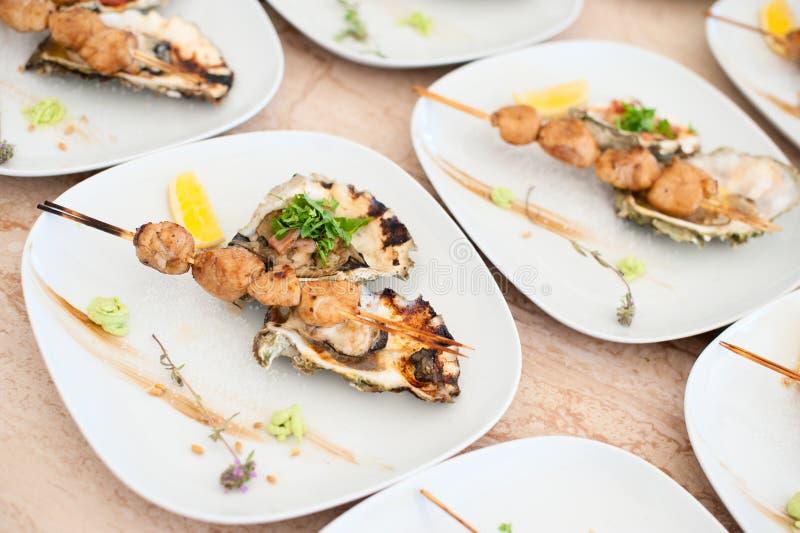 Prato com o no espeto das vieiras de mar e das ostras cozidas imagem de stock royalty free