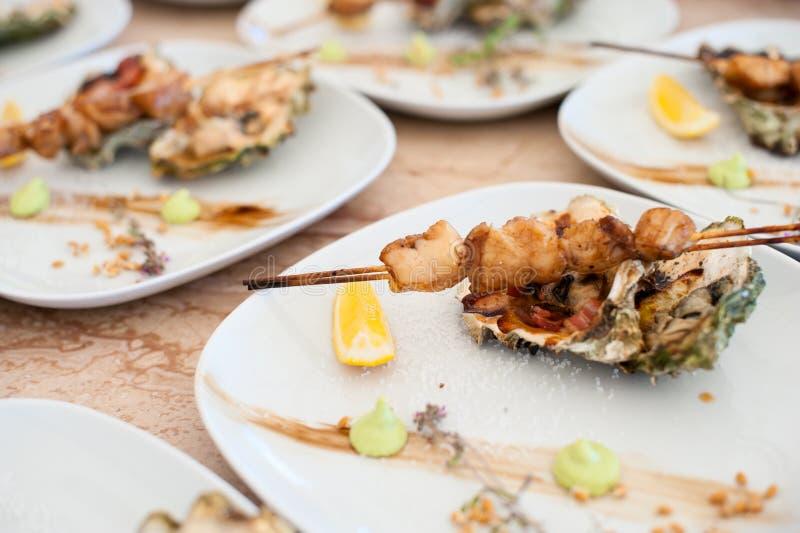 Prato com o no espeto das vieiras de mar e das ostras cozidas fotos de stock royalty free