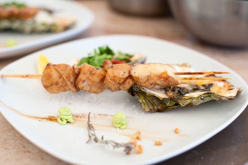 Prato com o no espeto das vieiras de mar e das ostras cozidas fotografia de stock royalty free