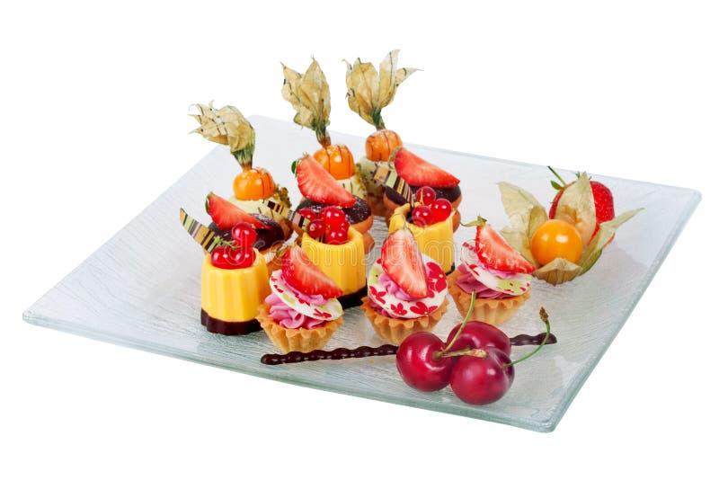 Prato com os mini bolos de chocolate creme e bagas fotografia de stock royalty free