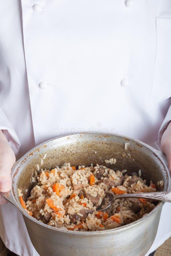 Prato com pilau nas mãos do cozinheiro fotos de stock royalty free