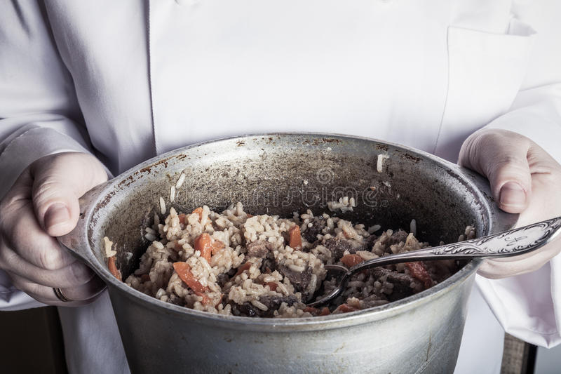 Prato com pilau nas mãos do cozinheiro toned fotografia de stock royalty free