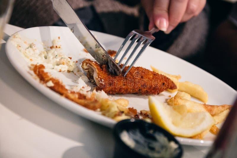 Prato comido metade do peixe com batatas fritas que está sendo cortado usando a cutelaria por um woma foto de stock