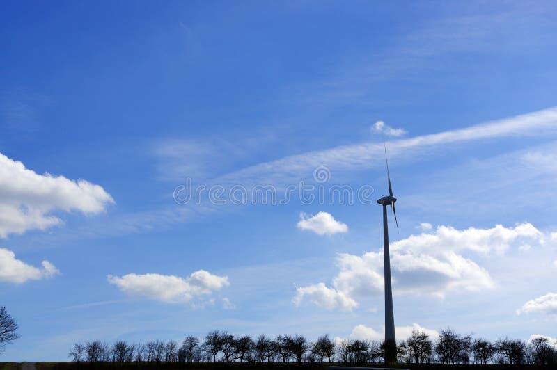Prato con i generatori eolici che generano gli alberi e gli skys di elettricità fotografia stock libera da diritti
