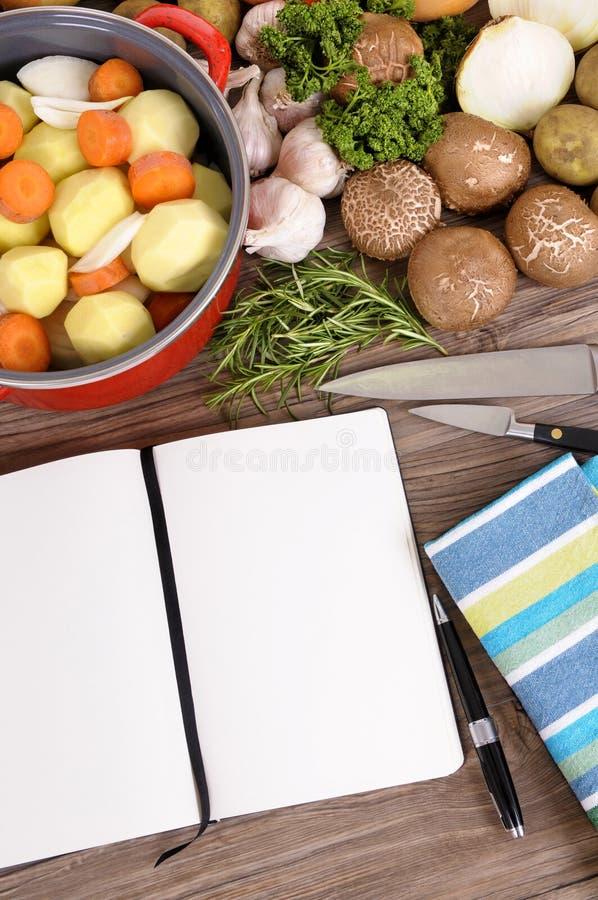 Prato da caçarola ou potenciômetro de guisado com vegetais orgânicos, livro de receitas na mesa de cozinha foto de stock royalty free