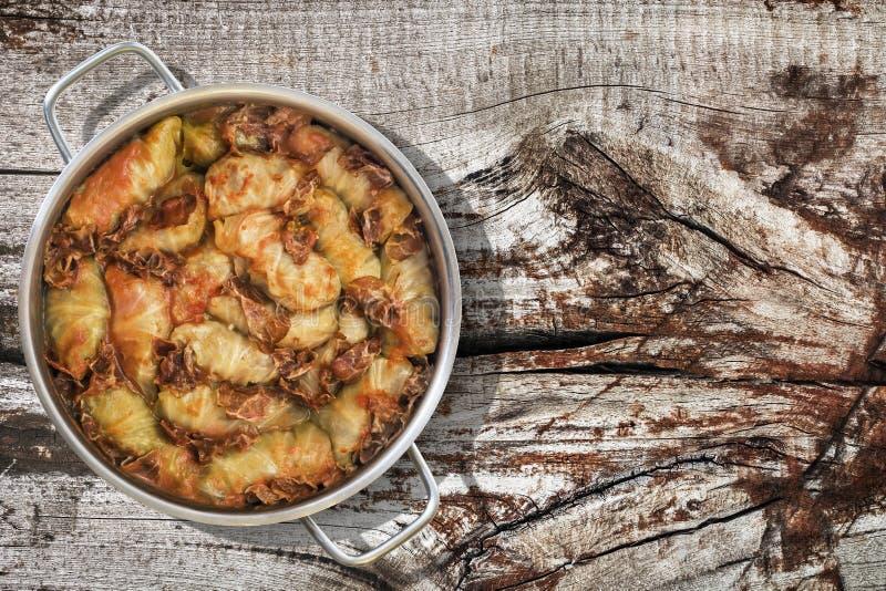Prato da couve conservada Rolls enchido com a carne triturada cozinhada em Saucepot de aço inoxidável servido na tabela de madeir fotografia de stock royalty free