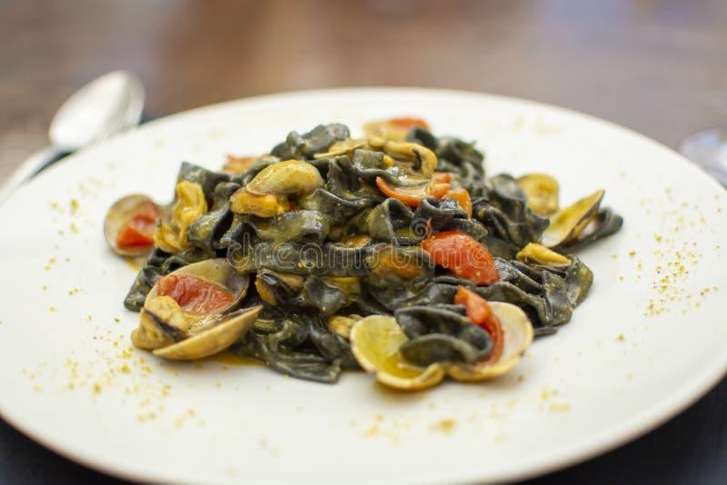 Prato da massa do marisco, fettuccini preto italiano com moluscos do vongole e mexilh?es fotos de stock royalty free