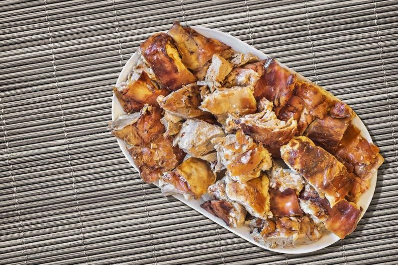 Prato das fatias Roasted cuspe da carne de porco ajustadas em Straw Place Mat Grunge Surface foto de stock royalty free